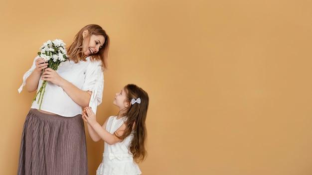 Mãe e filha com buquê de flores da primavera e espaço de cópia Foto gratuita