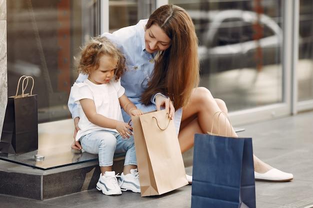 Mãe e filha com sacola de compras em uma cidade Foto gratuita