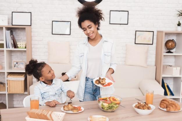 Mãe e filha comem juntos na cozinha. Foto Premium