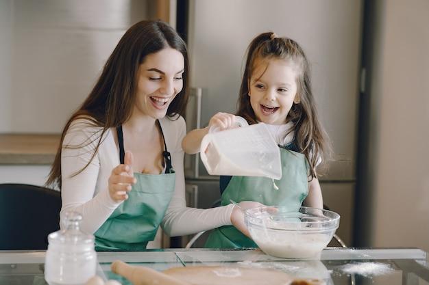 Mãe e filha cozinham a massa para biscoitos Foto gratuita