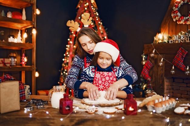 Mãe e filha cozinhando biscoitos de natal. Foto Premium