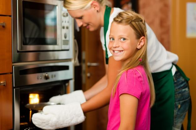 Mãe e filha cozinhando Foto Premium