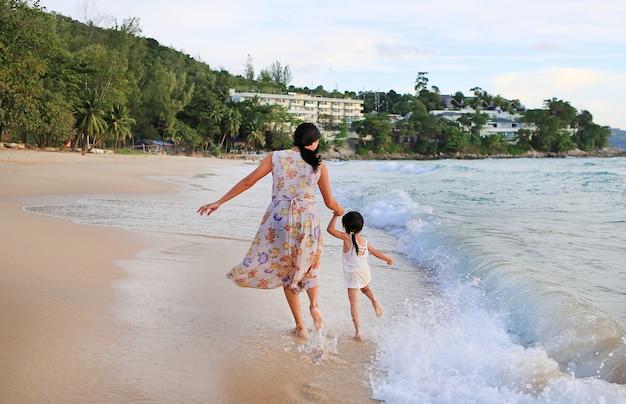 Mãe e filha da vista traseira que correm na praia. Foto Premium