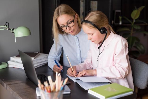 Mãe e filha de lado participando de uma aula on-line Foto gratuita