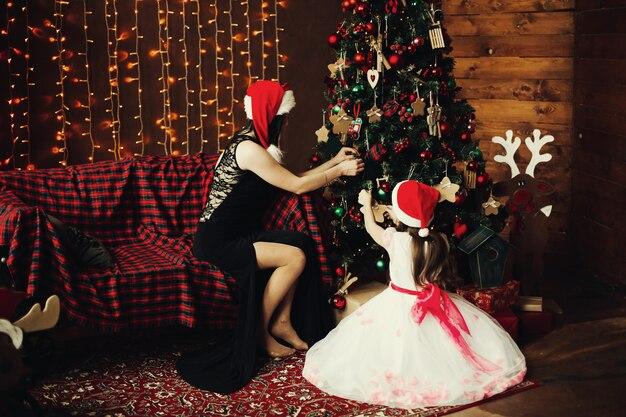 Mãe e filha decorando a árvore x mas para o ano novo e as férias de natal. Foto Premium