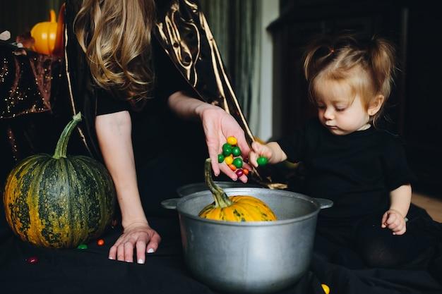 Mãe e filha decorar uma abóbora em uma bacia Foto gratuita