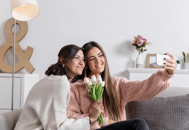 Mãe e filha em casa tomando selfie Foto gratuita
