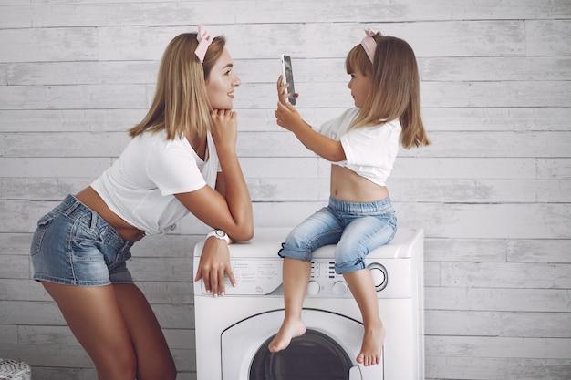 Mãe e filha em um banheiro perto de lavagem mashine Foto gratuita