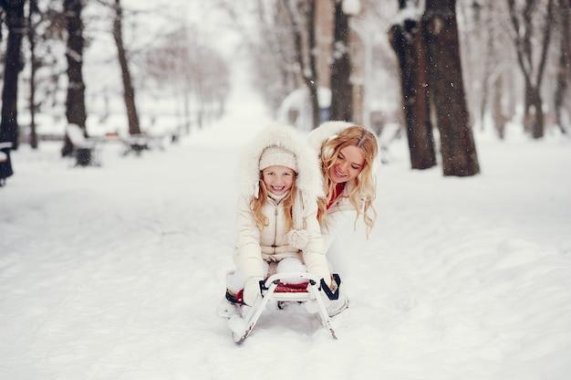 Mãe e filha em um parque de inverno Foto gratuita