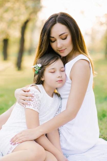 Mãe e filha em vestidos brancos em um piquenique no verão Foto Premium