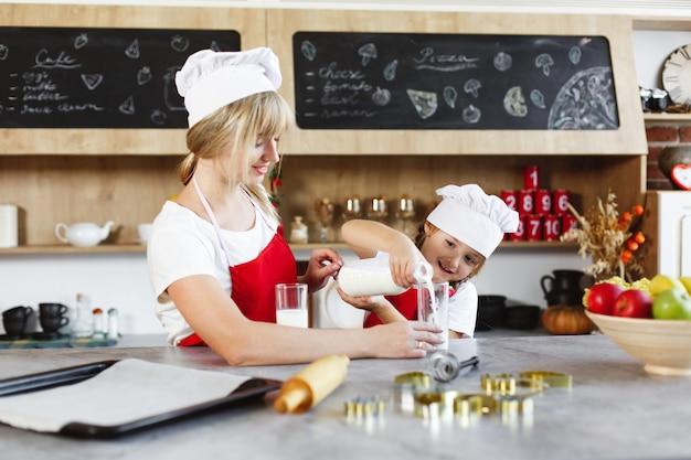 Mãe e filha encantadora se divertir bebendo leite na mesa em uma cozinha aconchegante Foto gratuita