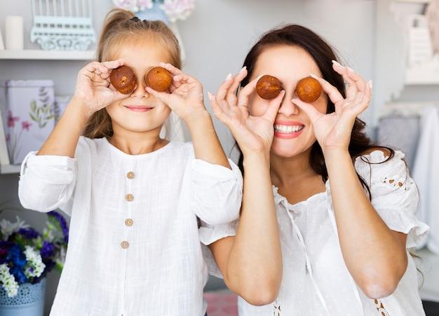 Mãe e filha engraçadas fazendo olhos de ovo Foto gratuita