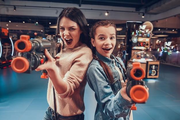 Mãe e filha estão atirando armas no arcade. Foto Premium