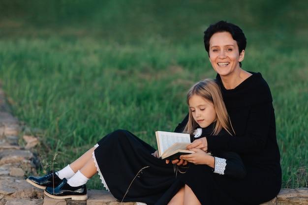 Mãe e filha estão sentadas em um banco de pedra e lendo um livro. mulher com uma criança em vestidos pretos. Foto Premium