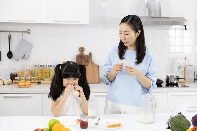 Mãe e filha estão tomando café da manhã na cozinha Foto Premium