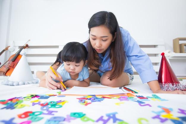 Mãe e filha estudando o alfabeto Foto gratuita