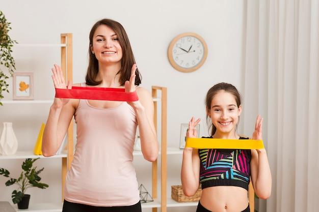 Mãe e filha exercitando com elástico Foto gratuita