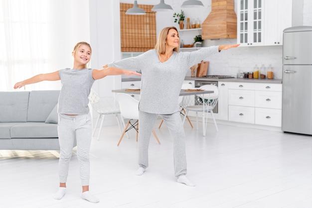 Mãe e filha fazendo exercícios de fitness Foto gratuita