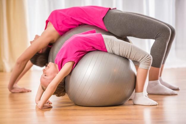 Mãe e filha fazendo exercícios físicos na bola de fitness Foto Premium