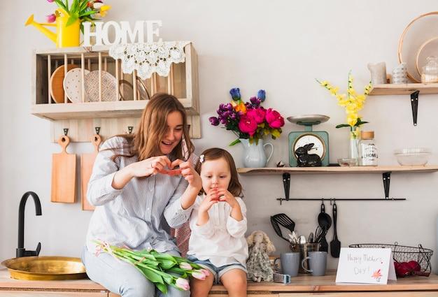 Mãe e filha fazendo formato de coração com as mãos Foto gratuita