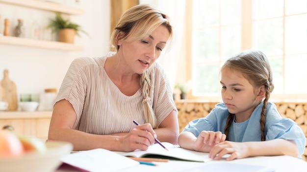 Mãe e filha fazendo lição de casa em casa Foto gratuita