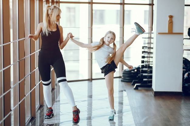 Mãe e filha fazendo yoga em um estúdio de yoga Foto gratuita
