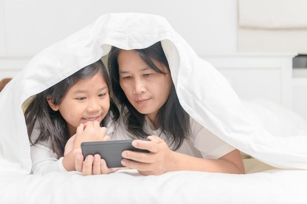 Mãe e filha jogam celular na cama Foto Premium