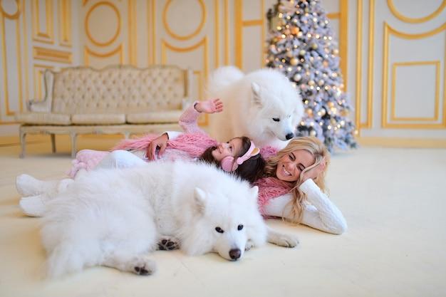 Mãe, e, filha, jogo, com, samoiedo, cachorros, antes de, um, árvore natal Foto gratuita