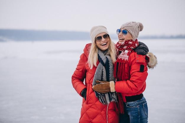 Mãe e filha juntos caminhando no parque no inverno Foto gratuita