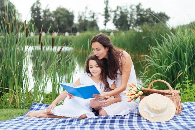 Mãe e filha lendo livro à beira do lago Foto gratuita