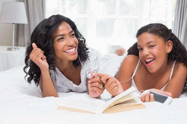 Mãe e filha lendo livro e ouvindo música juntos na cama Foto Premium