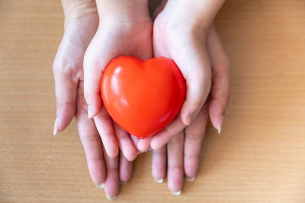 Mãe e filha mãos segurando um coração vermelho, cuidados de saúde, doar e conceito de seguro familiar Foto Premium