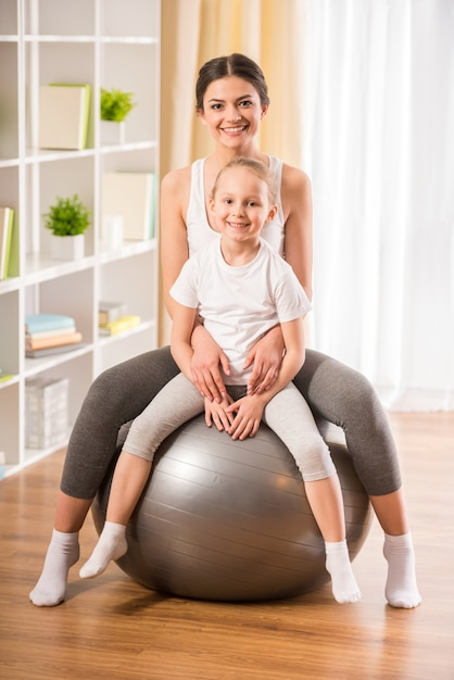 Mãe e filha na bola de fitness em casa. Foto Premium