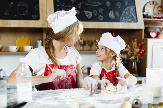 Mãe e filha nas mesmas roupas se divertem preparando uma massa em uma cozinha aconchegante Foto gratuita
