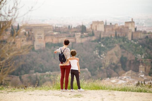 Mãe e filha olhando para a alhambra Foto Premium