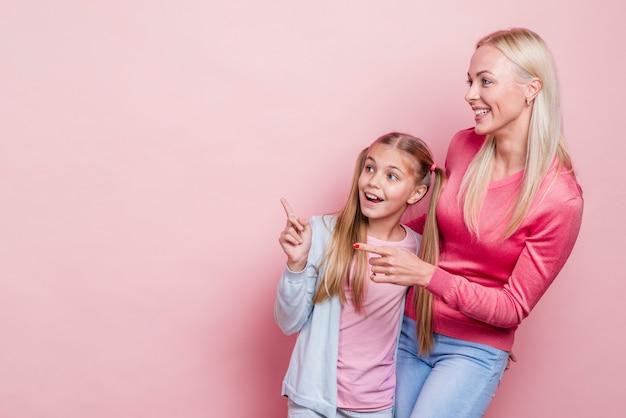 Mãe e filha olhando para longe e copie o fundo do espaço Foto gratuita