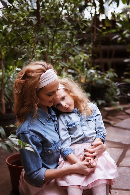 Mãe e filha. olhar familly. mulher abraça e beija a filha Foto Premium