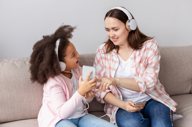 Mãe e filha ouvindo música em casa Foto gratuita