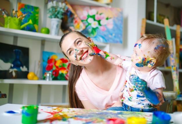 Mãe e filha pintam sobre tela na escola de desenho. Foto Premium