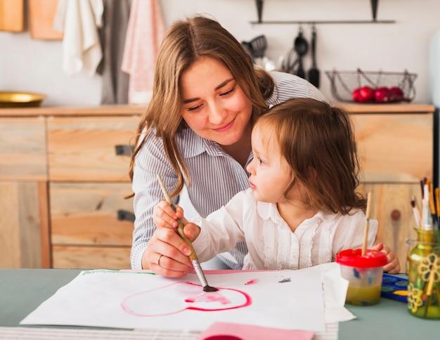 Mãe e filha pintando coração no papel Foto gratuita