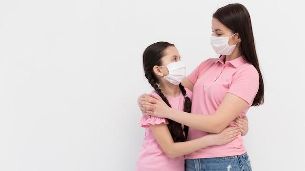 Mãe e filha posando dentro de casa Foto gratuita