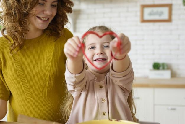 Mãe e filha preparam bolo juntas na cozinha Foto Premium