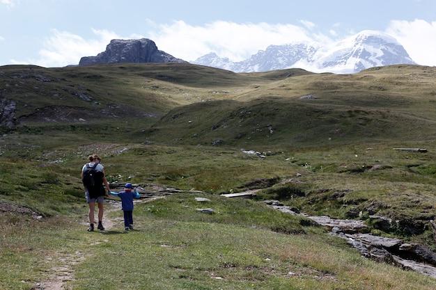 Mãe e filha que caminham nas montanhas alpinas perto de sunnega em suíça. Foto Premium