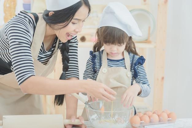 Mãe e filha que cozinham junto para fazer um bolo no quarto da cozinha. Foto Premium