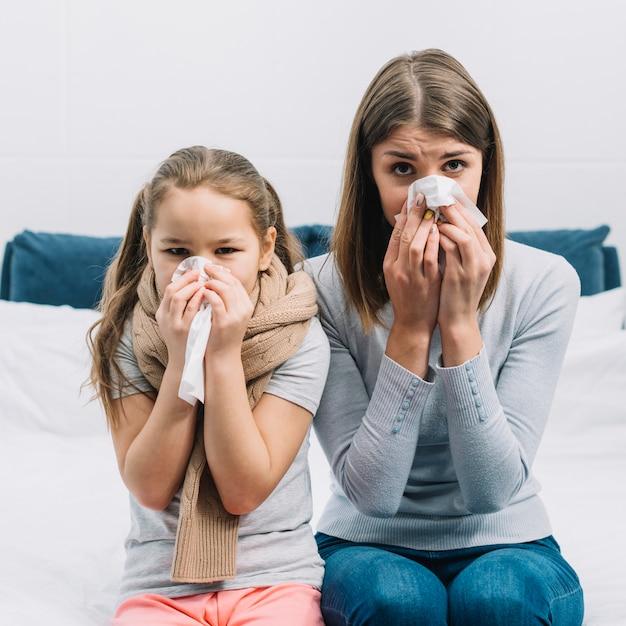 Mãe e filha que sofrem de frio e febre, cobrindo o nariz com lenço de papel Foto gratuita