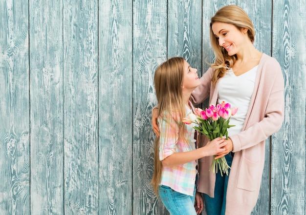 Mãe e filha satisfeita sorrindo e olhando para o outro Foto gratuita