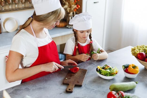 Mãe e filha se divertir na cozinha cozinhar legumes diferentes para um jantar Foto gratuita