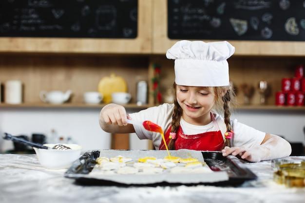 Mãe e filha se divertir preparando biscoitos com leite em uma mesa de jantar na cozinha aconchegante Foto gratuita