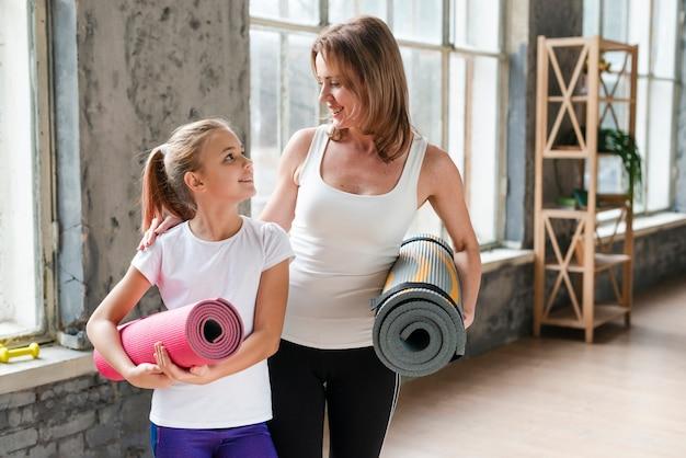 Mãe e filha segurando tapetes de ioga Foto gratuita