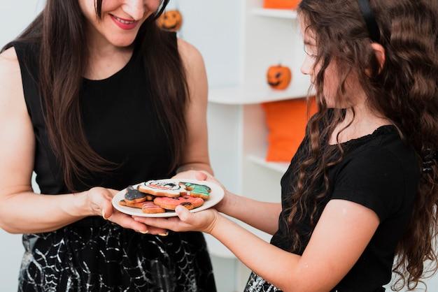 Mãe e filha segurando um prato com biscoitos Foto gratuita
